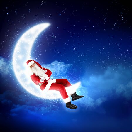 Photo of Santa Claus sitting on shiny moon above winter forest photo