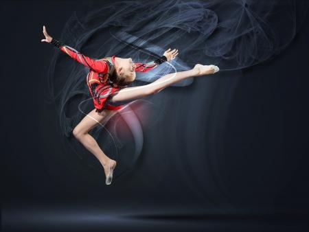 gymnastique: Jeune femme mignonne dans le costume gymnaste montrer comp�tences sportives sur fond noir