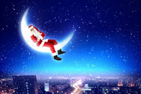 Santa Claus on the moon above a city at night photo