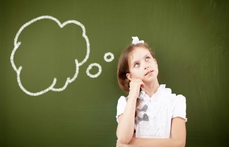 Scoolgirl standing in class near a green blackboard photo