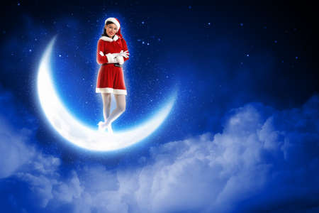 christmasbackground: Photo of Santa girl standing on shiny moon above winter forest