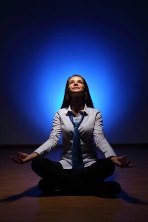 Young business woman sitting in asana lotus and meditating Stock Photo - 16716299
