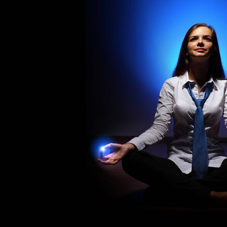 eyesclosed: Young business woman sitting in asana lotus and meditating