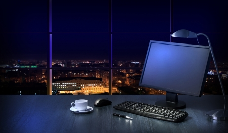 Work place in the office at night with a city view from window Stock Photo - 16697988