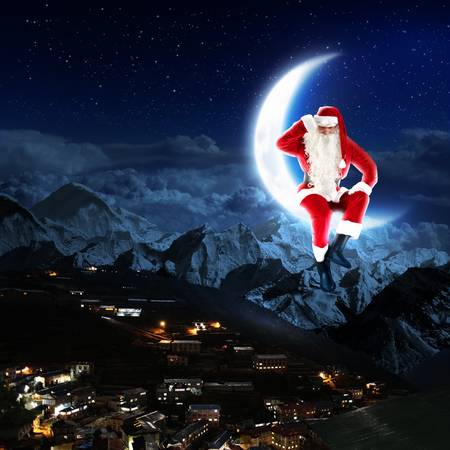 santa claus sitting on the moon with a city and mountains below photo