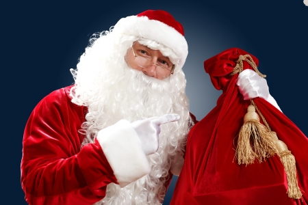 Santa Claus with his magic gift red bag full of presents Stock Photo - 16751851