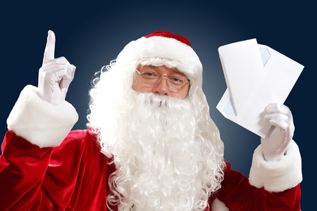 Santa Claus holding and reading a letter to him Stock Photo - 16751881
