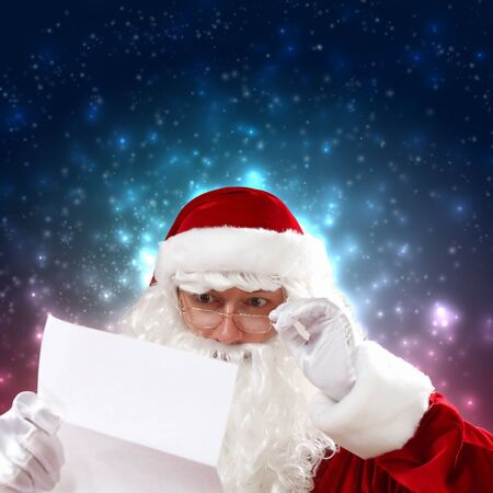 Santa holding Christmas letters and looking at camera photo