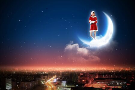 Santa Claus girl on the moon above a city at night Stock Photo - 16751538