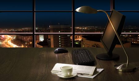 Work place in the office at night with a city view from window Stock Photo - 16737379