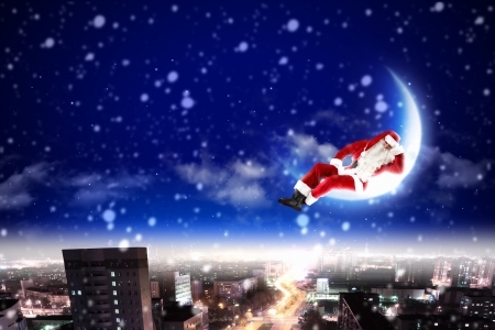 Santa Claus on the moon above a city at night Stock Photo - 16751472