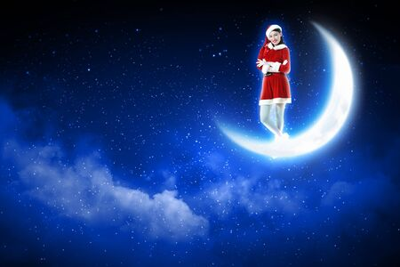 christmasbackground:  Santa girl standing on shiny moon above winter forest Stock Photo