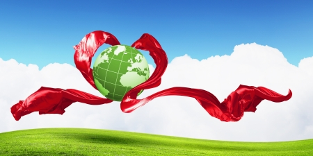 World within the heart symbol on blue sky background photo
