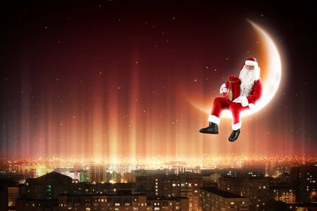 Santa Claus on the moon above a city at night Stock Photo - 16830109