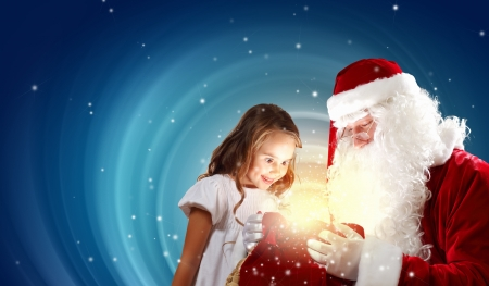Portrait of Santa Claus with a little girl looking at a gift Stock Photo - 16830119