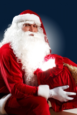 Santa Claus with his magic gift red bag full of presents Stock Photo - 16830090