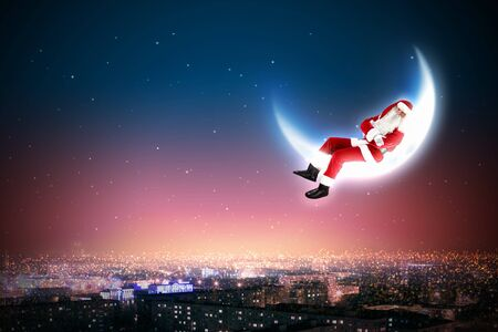 Santa Claus on the moon above a city at night Stock Photo - 16830108