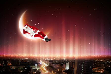 Santa Claus on the moon above a city at night Stock Photo - 16830074