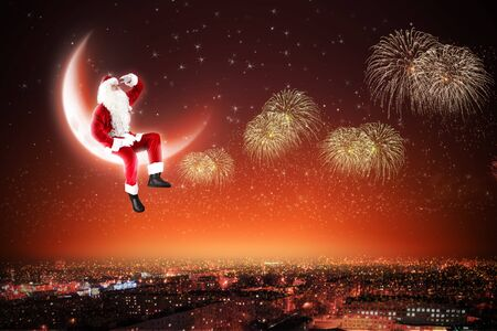 Santa Claus on the moon above a city at night Stock Photo - 16830069