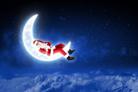 christmasbackground: Photo of Santa Claus sitting on shiny moon above winter forest
