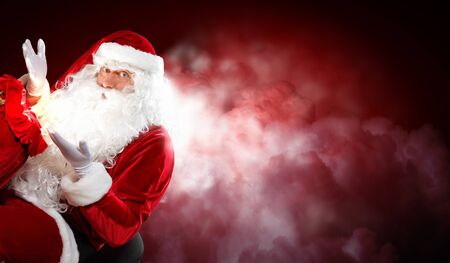 Santa with beard and red hat holding and looking into the sack Stock Photo - 16865670