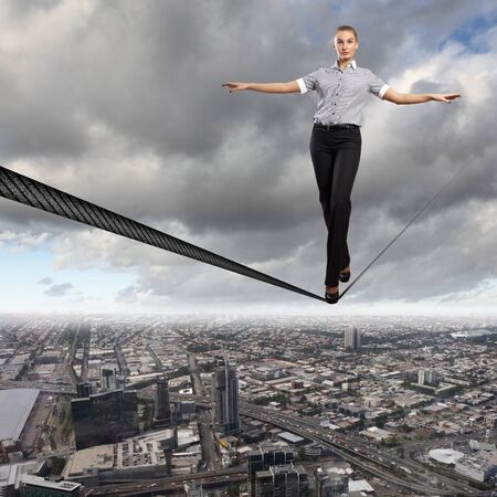 Business woman balancing high over a cityscape Stock Photo - 16866081