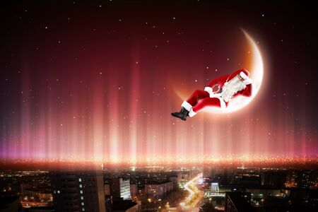 Santa Claus on the moon above a city at night Stock Photo - 16866000