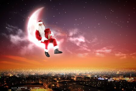 Santa Claus on the moon above a city at night Stock Photo - 16866360