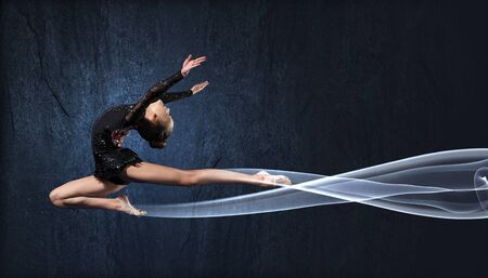 gymnast: Young cute woman in gymnast suit show athletic skill on black background