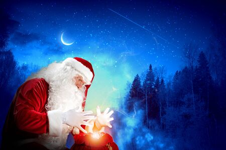 Santa with beard and red hat holding and looking into the sack Stock Photo - 16866378