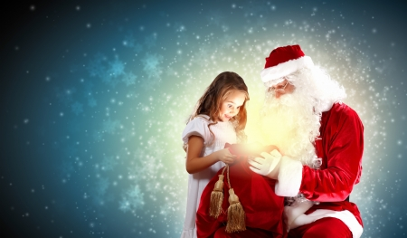 santa girl: Portrait of Santa Claus with a little girl looking at a gift Stock Photo