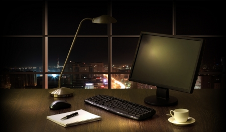 Work place in the office at night with a city view from window Stock Photo - 16866920