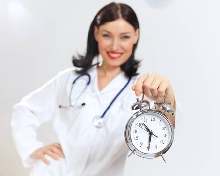 Portrait of happy successful young female doctor holding clocks Stock Photo - 16866254