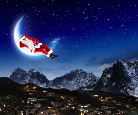 photo of santa claus sitting on the moon with a city and mountains below Stock Photo - 16866416