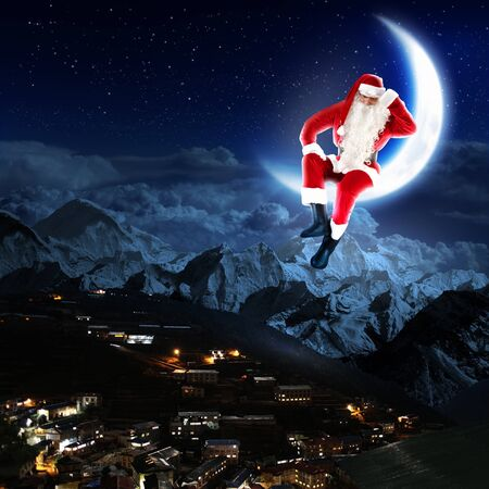 photo of santa claus sitting on the moon with a city and mountains below photo
