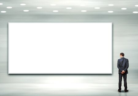 Business person standing near a white blank billboard photo