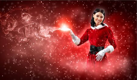 Portrait of beautiful girl wearing santa claus clothes on red background Stock Photo - 16884670