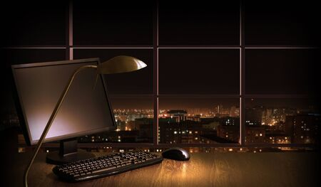 Work place in the office at night with a city view from window Stock Photo - 16896954