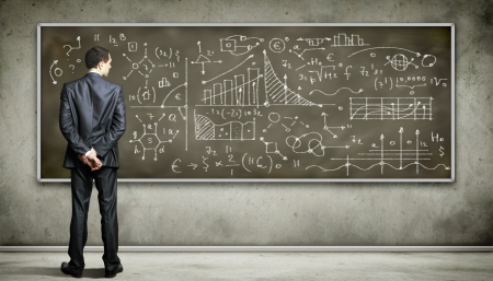 proof: Business person standing against the blackboard with a lot of data written on it