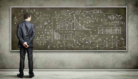 problemas: Personas de negocios de pie contra la pizarra con una gran cantidad de datos escrito en ?l Foto de archivo