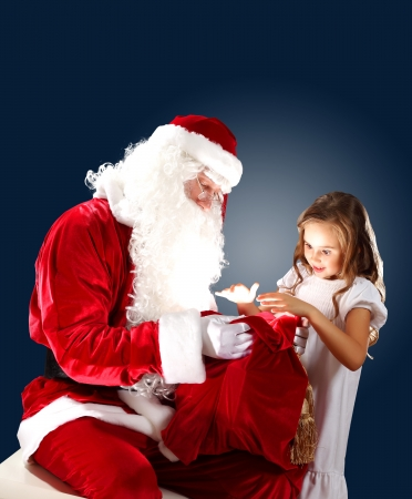 Santa Claus with his magic gift red bag full of presents Stock Photo - 16884685