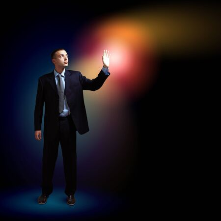 Young successful businessman holding a shining light in his hand as a symbol of success and advancement  photo