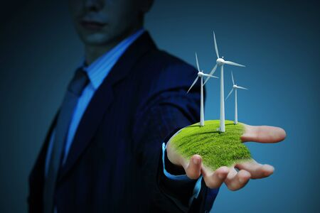 Business man and a windmills as a symbol of green energy Stock Photo - 16895705