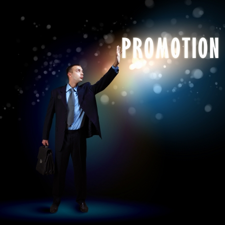 advancement: Young successful businessman holding a shining light in his hand as a symbol of success and advancement