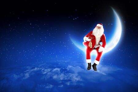 Santa Claus sitting on shiny moon above winter forest Stock Photo - 16906050