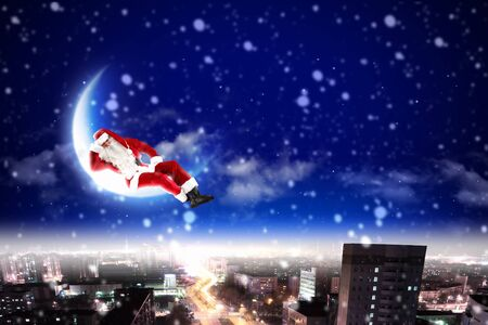 Santa Claus on the moon above a city at night Stock Photo - 16906740