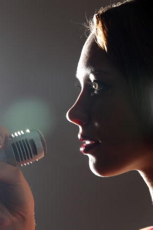 Portrait of female rock singer with microphone photo