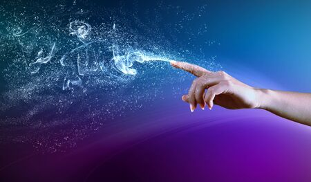 snapping fingers: magical hand conceptual image with sparkles on colour background
