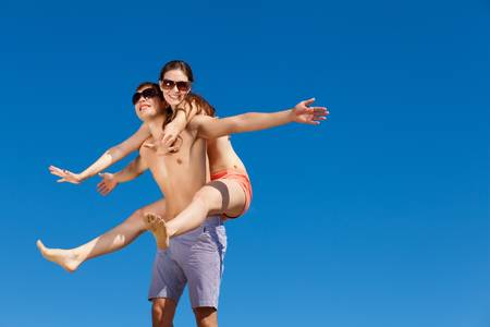 Portrait of a happy young couple enjoying at beach Stock Photo - 16951335