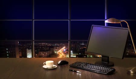 Work place in the office at night with a city view from window Stock Photo - 16952244